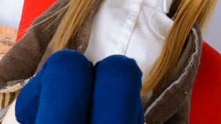 制服っぽい服を着たドールが両足を上げて座っている写真
