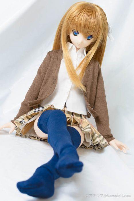 制服っぽい服を着たドールが両足を伸ばして座っている様子を前から写した様子