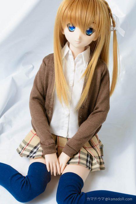 制服っぽい服を着たドールがぺたんこ座りをしているのを正面上から写した写真